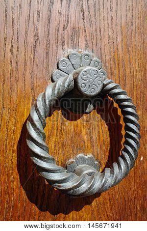Old ancient door knocker on wooden door Tuscany Italy