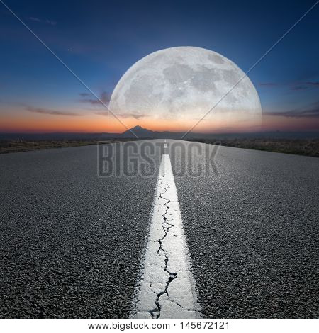 Empty highway leading to the mountains through the desert against the rising big full moon at night. Success concept.