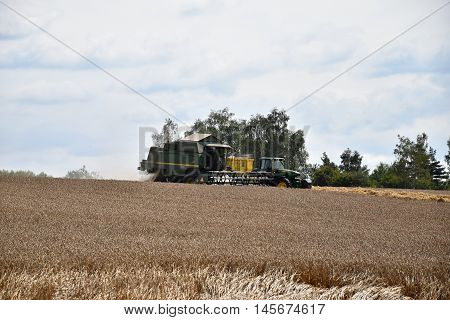 Combine Harvester pouring grain trailer behind a tractor