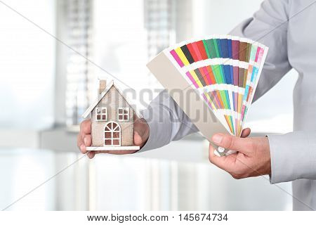 Hands with house and swatches interior design concept