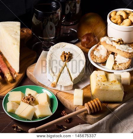Different types of cheese on wooden boards with wine, honey and walnuts on dark background. Square image
