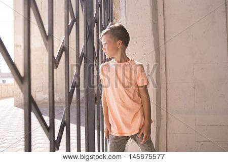 Trendy boy with cool hair leaned on the gate and looks through them . Stylish kid
