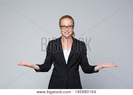 Beautiful young businesswoman smiling, holding open palms with empty copy space. Business woman showing hands sign to sides, concept of advertisement or comparing products. Grey background.