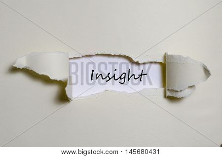 The word insight appearing behind torn paper
