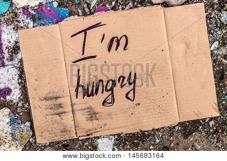 Cardboard with request for food donation on the ground.