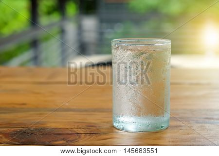 Glass water with drops on glass places on wooden table.