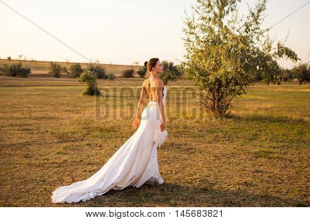 Young bride in white dress with a long train