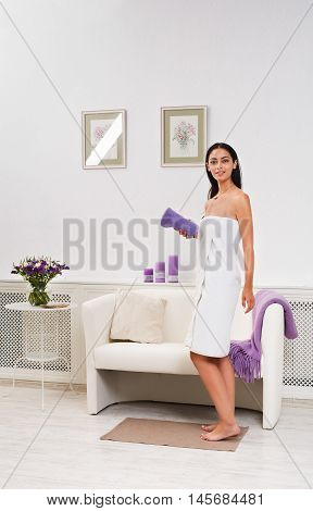 Full-length portrait of woman patient in spa wellness center interior. Young beautiful indian girl, long-haired brunette, dressed in white towel in cosmetology cabinet or beauty parlor. Vertical image
