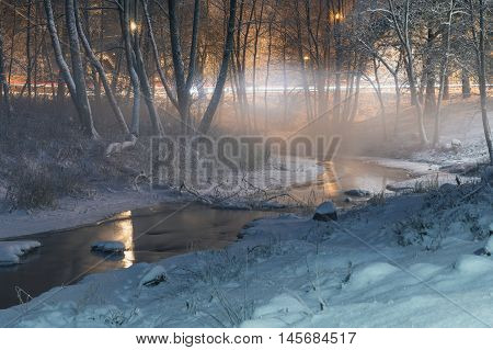Winter-time fog over small brook in park by night. Roadway with head lamp lights. Long exposure image.