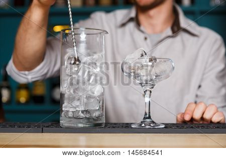 Barman's hands in bar interior making alcohol cocktail. Professional bartender at work in bar mixing ice in glass for drink. Party time in night club