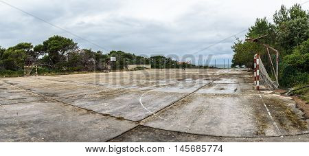 Old abandoned school sports court or schoolyard for different activities. Ruins of a sport venue abandoned long time ago with soccer handball or football goals basketball hoops and boards and destroyed concrete plates.