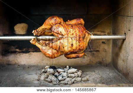 Cooking and preparing rotisserie chicken on the grill with Charcoal and Briquettes in the professional steak house or barbecue restaurant