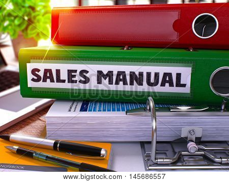 Sales Manual - Green Office Folder on Background of Working Table with Stationery and Laptop. Sales Manual Business Concept on Blurred Background. Sales Manual Toned Image. 3D.