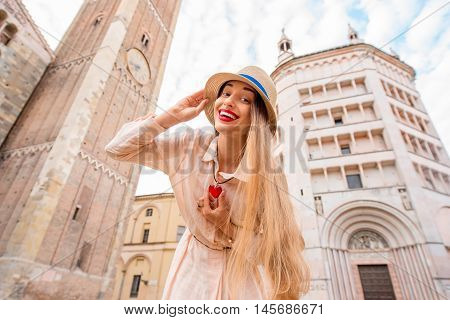 Young female positive tourist standing on the central square with cathedral and famous leaning tower on the background in Parma town. Having great vacations in Parma