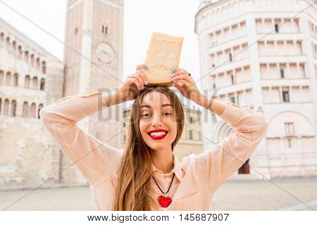 Young woman holding a piece of Parmesan cheese at the main square in Parma town in Italy. Parmesan is produced mostly in the province of Parma and was named after that producing region
