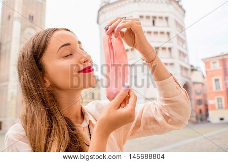 Young woman with prosciutto on the main square in Parma town in Italy. Parma is a city in the north of Italy famous for its prosciutto ham