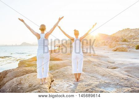 Caucasian woman practicing yoga at seashore,   dressed in white