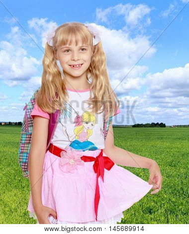 Cheerful little girl in a pink short skirt with a knapsack on his shoulders. Close-up.On the background of grass and blue sky with clouds.
