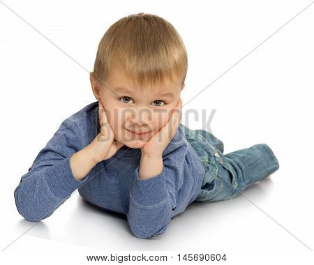 Little boy in jeans and a sweater lying on the floor , he put his head in his hands - Isolated on white background