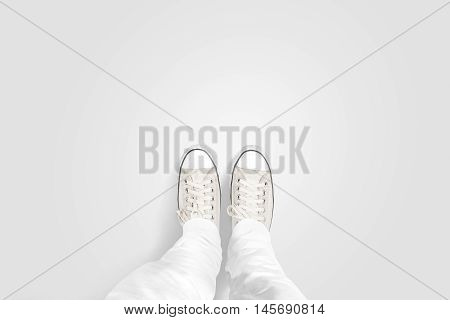 Person taking photo of his foots stand on blank floor, isolated, top view, clipping path. Ground design mock up. Man wear gumshoes and watching down. Deck flooring mockup template.