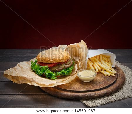 Fast food dish. Meat burger and potato chips on wood. Takeaway composition. Wrapped French fries, hamburger in kraft paper and mayonnaise sauce on wooden desk.