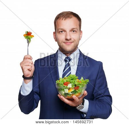Healthy food and diet concept. Young businessman holds fork to eat fresh vegetable salad meal isolated on white background. Modern dieting and weight loss nutrition for busy men.