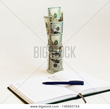 On a light background is open daily with a ballpoint pen. before the diary is a glass jar from which protrude banknotes.