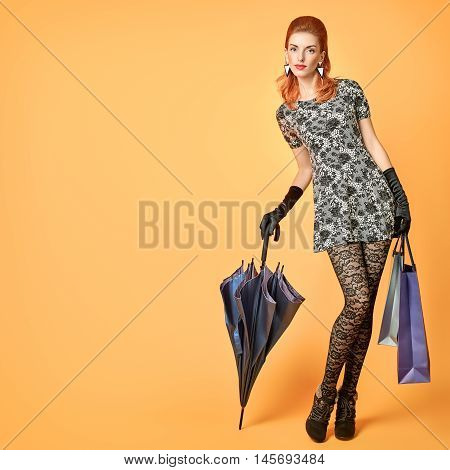 Fashion beauty Sexy Woman.Stylish Autumn Outfit with Shopping bags, umbrella.Model Redhead girl in stockings.Unusual fall fashion creative vogue.Glamour fashion discount concept on orange.RetroVintage.