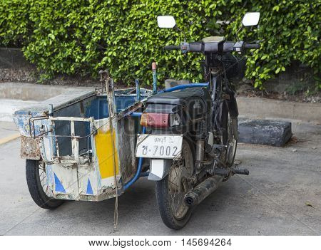 Pattaya, Thailand - Jul 17, 2015: Close up of a D.I.Y tri wheel motorcycle used to transport good and product on a side walk of a street in Pattaya.