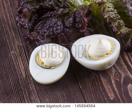 The Two Halves Of An Egg With Mayonnaise Lettuce On A Wooden Background. Eggs.