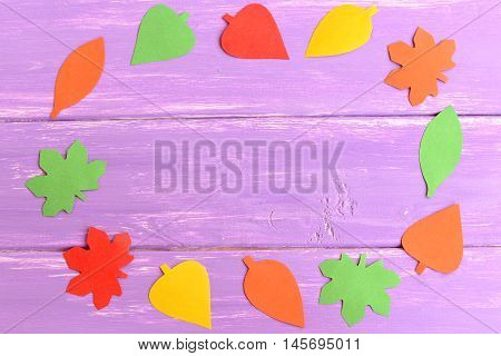 Fall leaves cut from colored paper. Yellow, red, green and orange paper leaves on blue wooden background with copy space for text. Fall background for kids, preschoolers. Top view