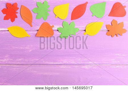 Bright autumn background for kids, kindergarten. Yellow, green, red, orange leaves cut from colored paper. Autumn paper leaves on blue wooden background with blank space for text. Top view