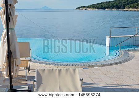 Empty infinity pool on the sunrise, quiet bue sea