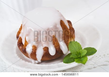 Rum baba cake on plate on light background