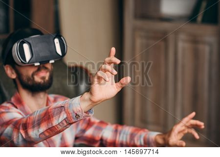 Man in vr goggles touching something, void. Blurred background of male in virtual reality headset. focus on finger pushing invisible icon