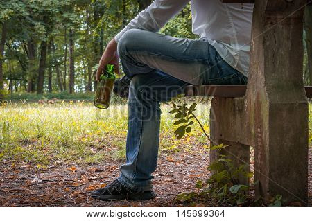 Depressed Drunk Man With Beer Bottle Sitting On Bench