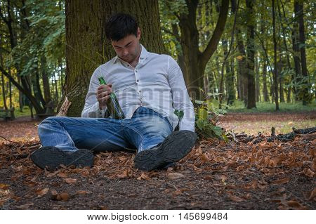 Drunk Man Lies On The Ground Under The Tree With A Beer Bottle