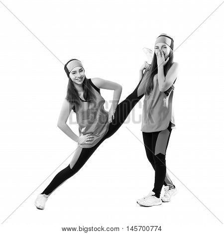 Two young professional cheerleader are stretched before performance. Isolated over white. Black and white photography