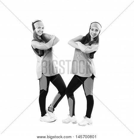 Two young professional cheerleaders posing at studio. Isolated over white. Black and white photography