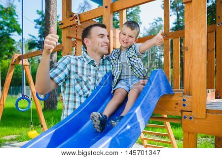 Happy kid and father having fun. Child with dad playing outdoor. Boy sitting on children's slide.