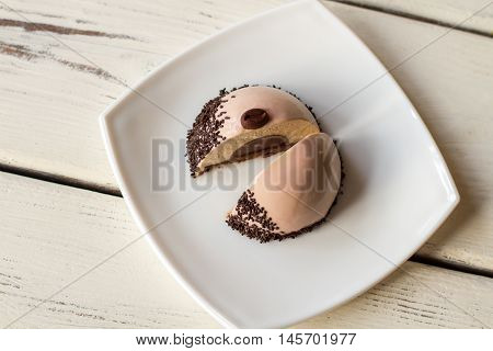 Small cake with brown filling. Two halves of glazed dessert. Fresh coffee mousse cake. Snack from pastry shop.