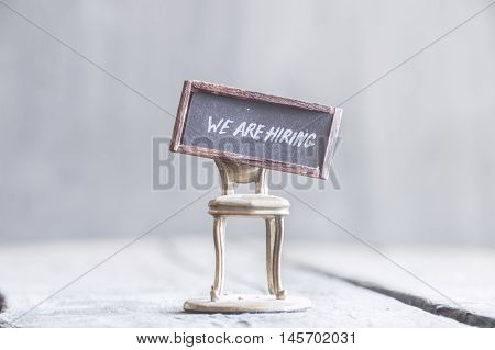 text We're hiring, the inscription on the label and golden chair