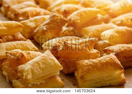 Puffs on light wooden board. Baked products under sunlight. Pastry of airy dough. Warm and delicious snack.