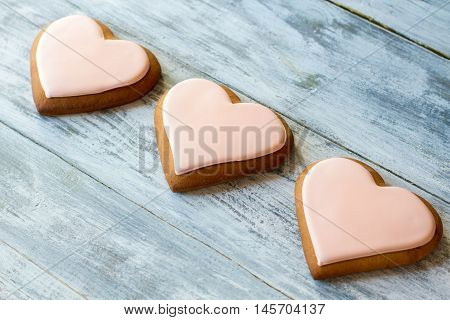 Three heart-shaped cookies. Biscuits with light pink glaze. Lots of love. Sweet treats for loved ones.