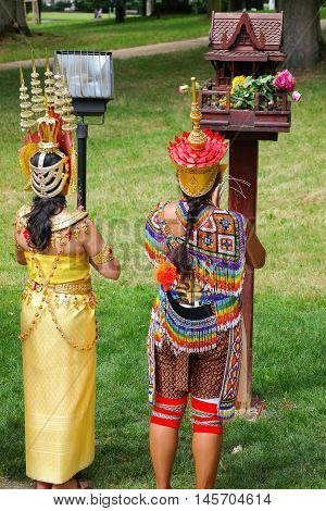 Two Thai women in colorful traditional Thai costumes during praying outdoors