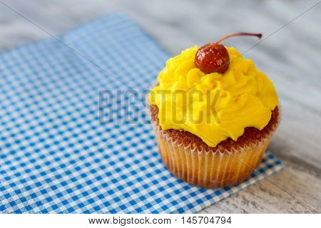 Cupcake on a napkin. Cherry and yellow icing. Dessert at the diner. Pastry made of organic ingredients.