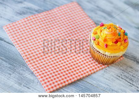 Cupcake on red checkered napkin. Pastry with orange icing. Try new dessert in diner. Small sugar flowers.