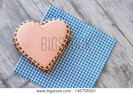 Top view of heart cookie. Glazed biscuit on checkered napkin. Love of a gourmet. Stay true to your feelings.