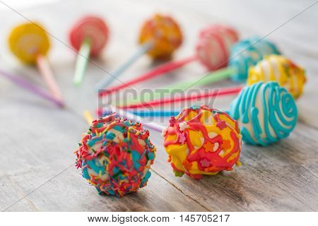 Candies with bright-colored icing. Sweets on gray background. Custom made cake pops. Flavors and colors.