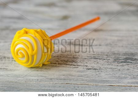 Cake pop with yellow icing. Candy lying on gray surface. Proven recipe of good mood. Sweeten up your day.